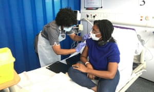 A volunteer receives the first vaccination as part of the Novavax vaccine phase 3 trial in London.