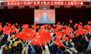 College students wave national flags as they watch the opening of the 19th Communist party congress in Huaibei in China's eastern Anhui province.