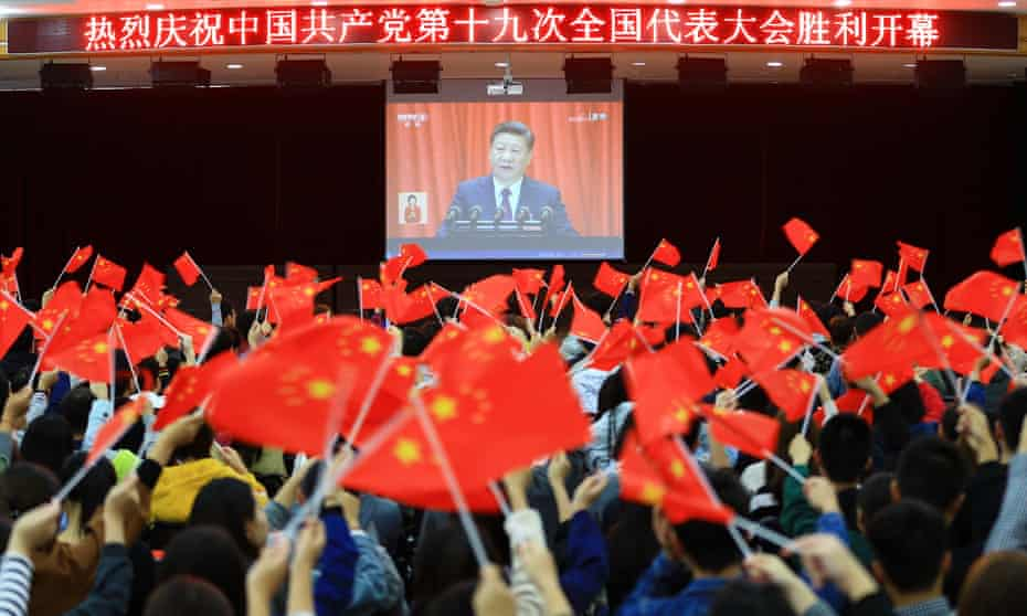 College students wave national flags as they watch Xi Jinping speak at the opening of the 19th Communist party congress in Huaibei, in China's eastern Anhui province.