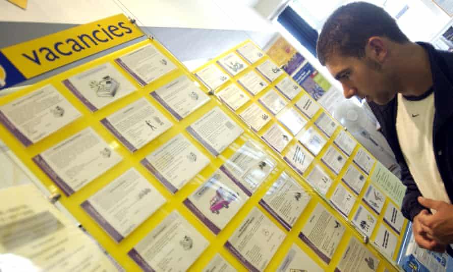 A man looks at a vacancies board in a Jobcentre