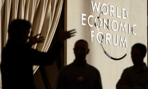People discuss in front of a WEF logo inside the Congress Center, two days before the opening of the 46th Annual Meeting of the World Economic Forum, WEF, in Davos