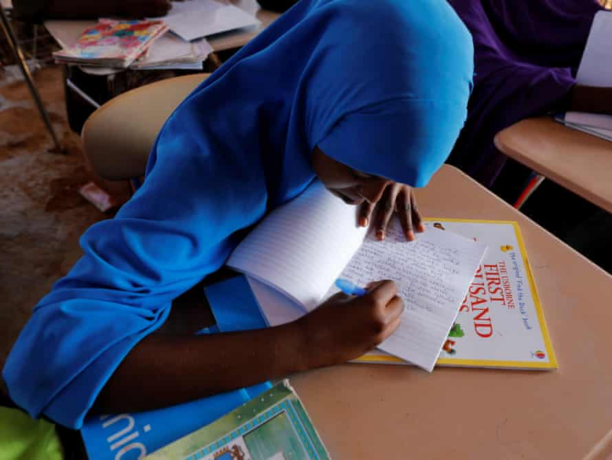 Zeinab writes in class at a school.
