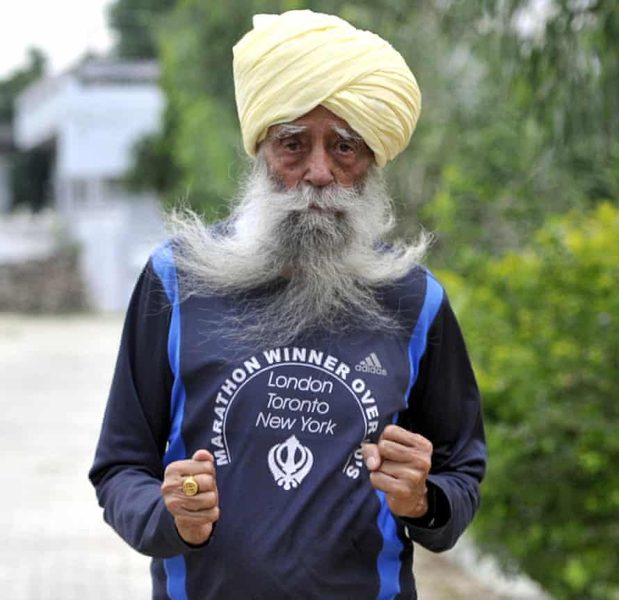 Fauja Singh, fists pumping out on a street, wearing a 'marathon winner' sports top, and with a turban and long grey beard.