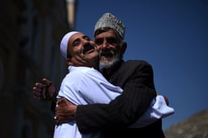 Men hug each other after offering prayers at the Shah-e Do Shamshira mosque