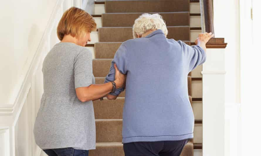 An older person is assisted up some stairs