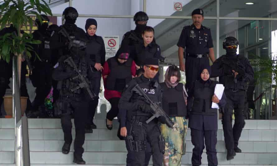 Doan Thi Huong and Siti Aisyah being escorted out of a courthouse by armed guards.