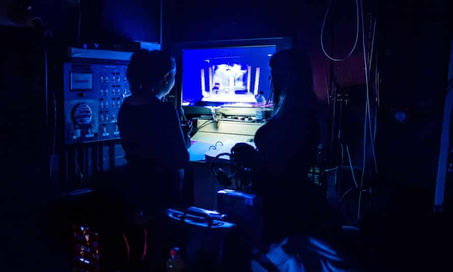 Two stage managers in the wings of a theatre production looking at a video monitor of the performance