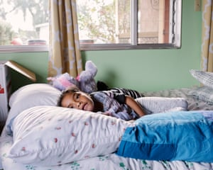 Juan Antonio's daughter Lesly, rests in the bed she shares with her father at their host's home.