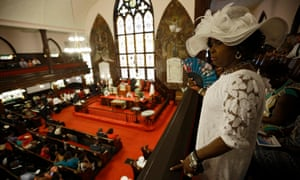 Gloria Moore watches as parishioners take their seats