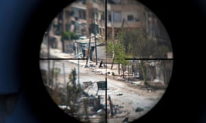 A woman and her baby are caught in the scope of an opposition fighter's gun as she flees the Saif al-Dawla neighbourhood of Aleppo, August 2012.