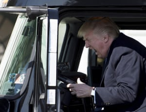 Donald Trump sits in the driver's seat of a vehicle as he welcomes truckers and CEOs to the White House on 23 March