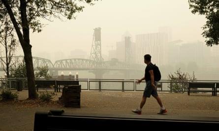 A pedestrian walks past the Willamette Bridge and downtown Portland, Oregon, on Wednesday.