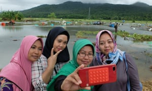 Solihat and her friends pose for a photo in front of the devastated field in Banten province.