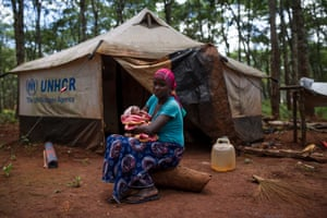 Nduyimana Gloriose, 21, sits for a portrait with her one month old son, Iriho Brian Kelly, outside their tent in Nduta