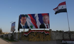 Assad and Putin watch over from billboards between the east and west of the city.