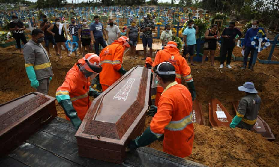 Gravediggers carry a coffin during a collective burial of people who have died due to Covid-19, at the Parque Tarumã cemetery in Manaus on Tuesday.