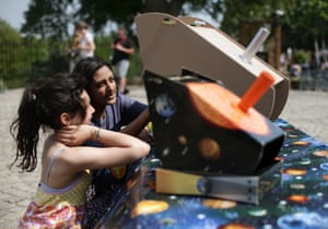 A staff member shows a visitor how to use a solar scope to see Mercury at The Royal Observatory in Greenwich, London, UK