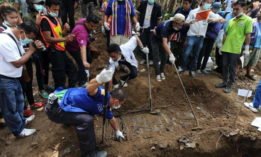 Rescue workers and forensic officials exhume skeletons from shallow graves covered by bamboo in Thailand's southern Songkhla province.