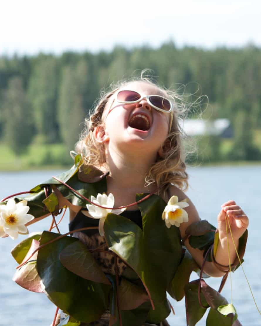 A girl with sunglasses with her head back laughing as she is covered in flowers standing in front of a lake