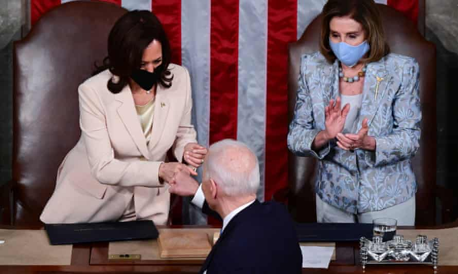 Vice-president Kamala Harris gives Joe Biden a fist bump as House speaker Nancy Pelosi looks on.
