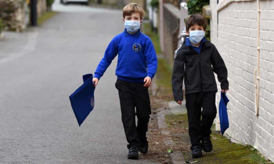 Children walking to school wearing smog pollution masks in the UK