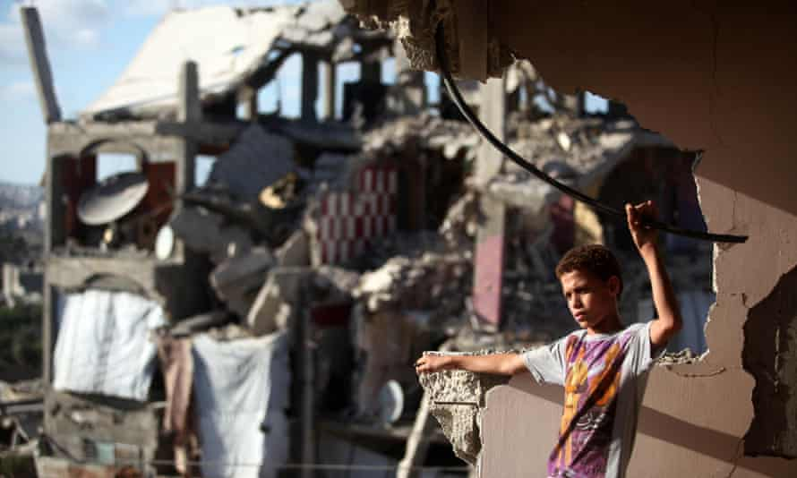 A Palestinian boy in the remains of a house hit by Israeli shelling during the 2014 Gaza conflict
