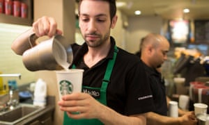 An employee pours milk into a coffee cup in a Starbucks in London, 2014