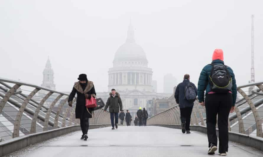 People cross the Millennium Bridge in London near St Paul's while freezing fog covered the capital on Monday.