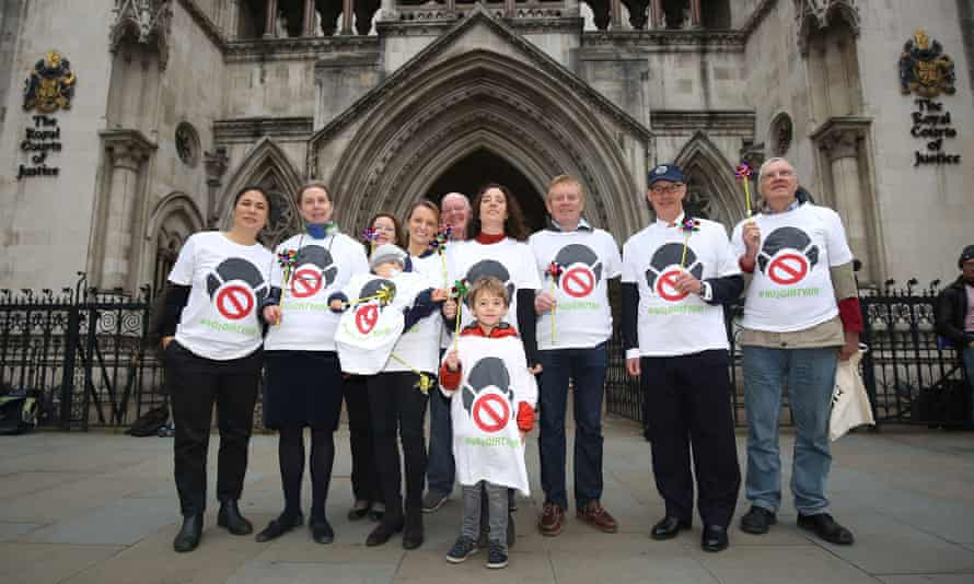 Supporters of a new legal challenge against the government over air pollution levels outside the high court in London.