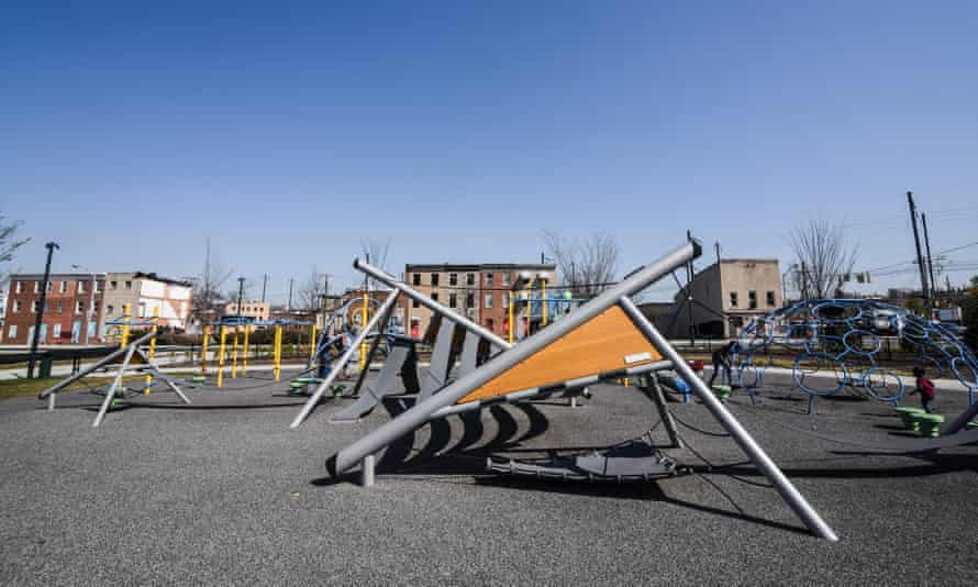 A row of abandoned homes border Eager Park's playground, Baltimore, which was opened news in 2017