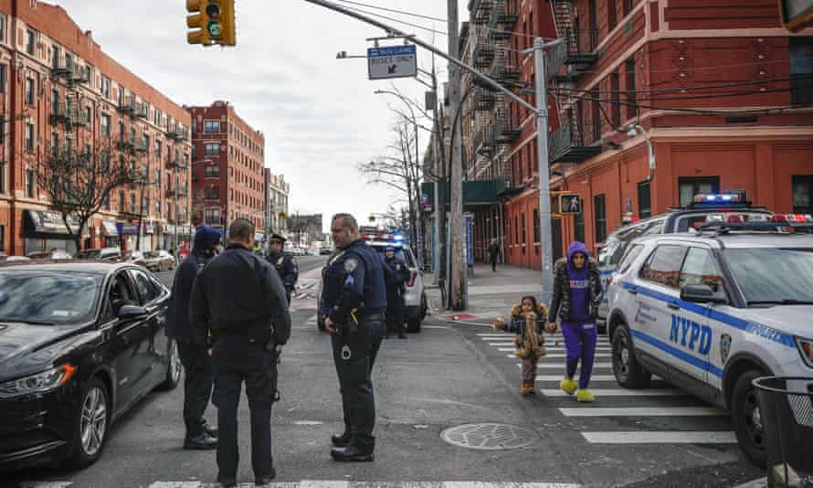 Police officers stand on the corner of 163rd and Fox Street at the scene of a police-involved shooting in the Bronx, New York, on 9 February.