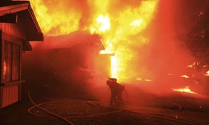 A firefighter struggles to protect a home from catching fire in Coffey Park, 9 October 2017 in Santa Rosa, California.