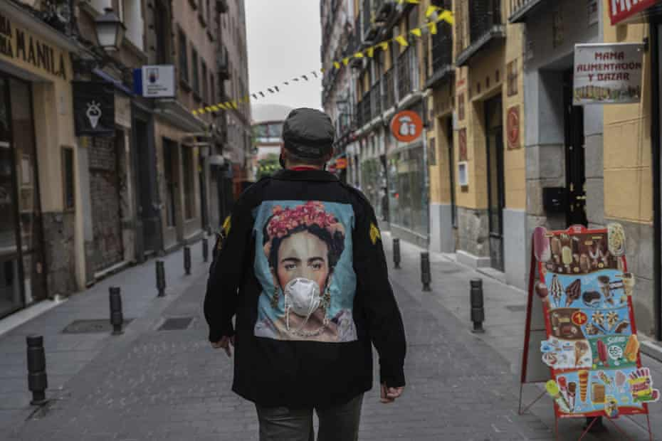 A man wearing a customised jacket with the image of Mexican artist Frida Kahlo wearing a face mask walks through central Madrid, Spain