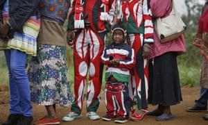 A boy stands with his parents, all wearing suits in the colours of the Kenyan flag, as they wait to vote in Gatundu, north of Nairobi.