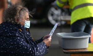 A member of the public reading an instruction sheet before taking a coronavirus test today at a temporary Covid testing facility in Manchester.