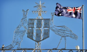 The Australian flag flies behind the coat of arms