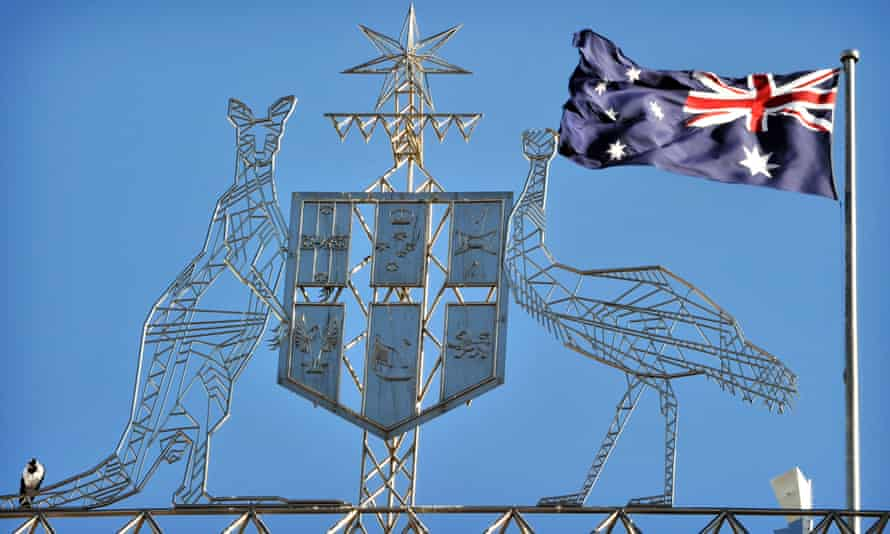 The Australian flag flies behind the coat of arms of Australia above Parliament House in Canberra