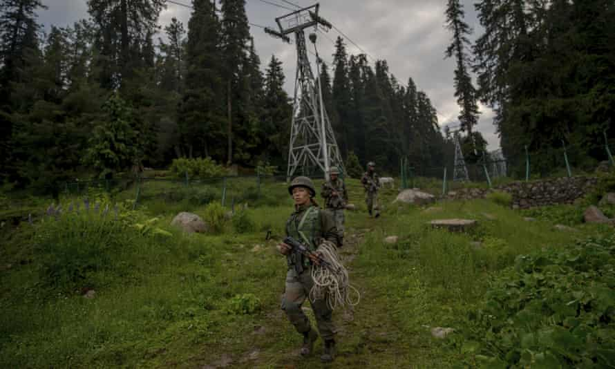 Indian army soldiers walk back after a rescue mission in Gulmarg.