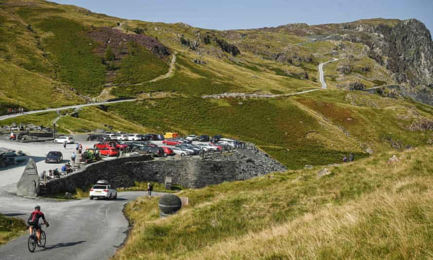 A cyclist passes the busy car park at the slate mine on Honister Pass in the Lake District.