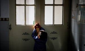A child tries to open a door at a home for at-risk youth run by the San Jose Providente Foundation, in the city of Jose C. Paz, Buenos Aires Province, Argentina