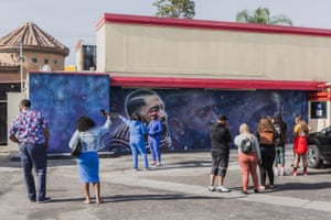 Fans come to take pictures and pay their respects to in front of the Nipsey Hussle murals on Wednesday.