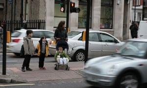 Children cross the road in heavy traffic outside their school in Hackney, London