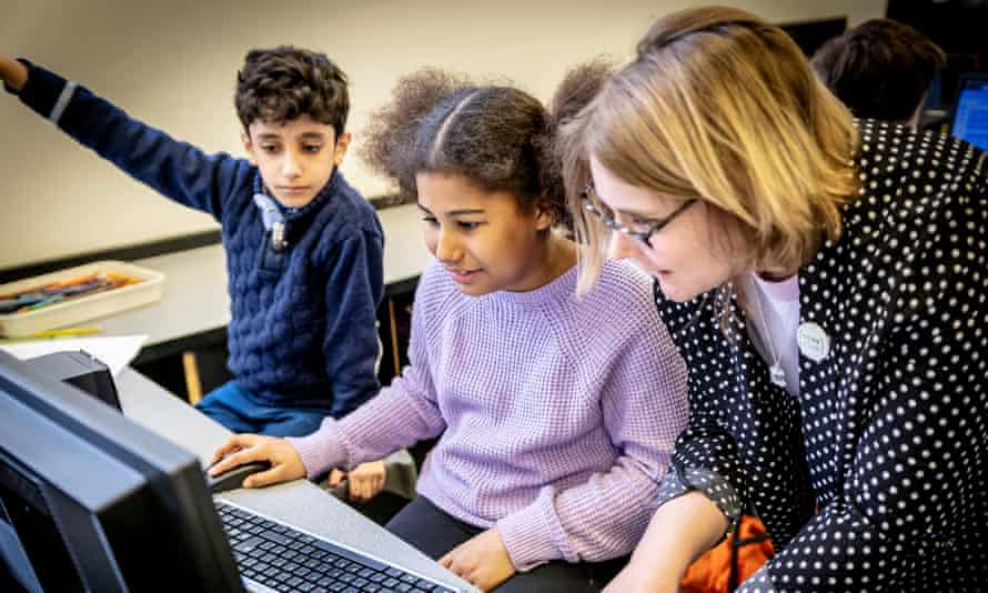 Code Club volunteer with a young boy and girl