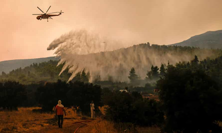 A firefighting helicopter makes a water drop as a wildfire burns in the village of Vilia, Greece, on August 18, 2021.