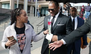 A fan hands singer R Kelly a rose after his court date at on 22 March in Chicago, Illinois.