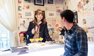 Eighteen-year-old cafe worker Airi chats with a customer. She is not a high school student, but she says wearing the uniform at the cafe makes her more popular.