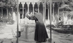 A still from Mallorca shows a monk drawing water from a well.