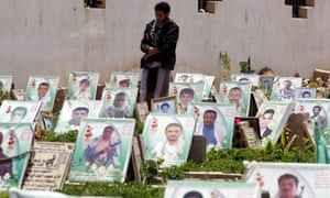A Houthi supporter walks among graves in Sana'a