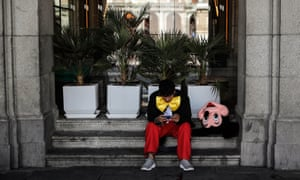 A street performer sits idle in Madrid.