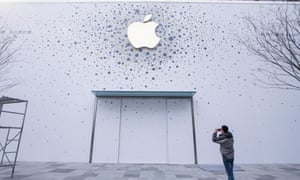 A man takes a photo of an almost completed Apple store in Hangzhou, Zhejiang province of China.